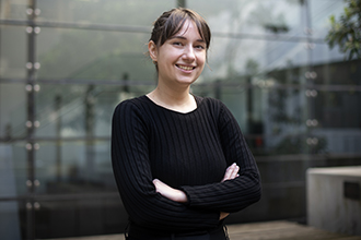 Researcher with crossed arms, smiling at camera