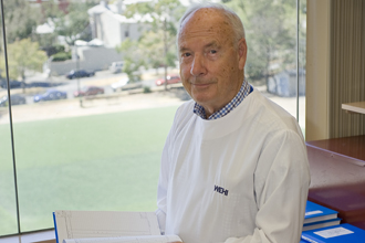 Professor Don Metcalf stands in his office with a lab notebook