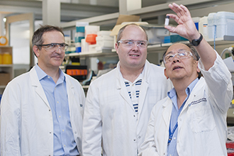 Associate Professor Guillaume Lessene, Dr Ueli Nachbur and Professor Andrew Lew looking at a vial in a laboratory