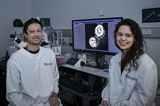 Smiling researchers with microscope