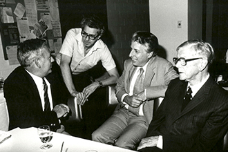 Black and white image of four men talking