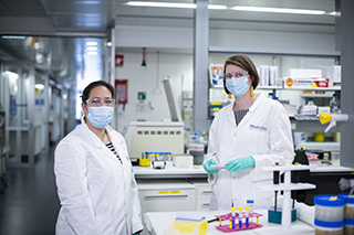 Two scientists in a laboratory wearing facemasks, lab coats and safety glasses