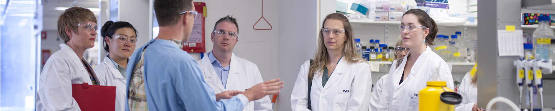A scientist talking to a group in a lab