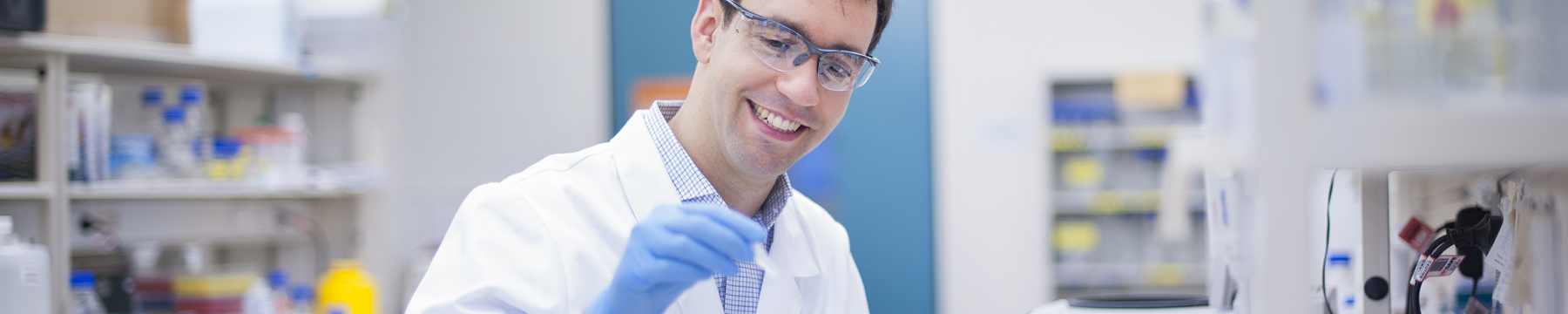 Scientist looking at sample in lab sitting at bench