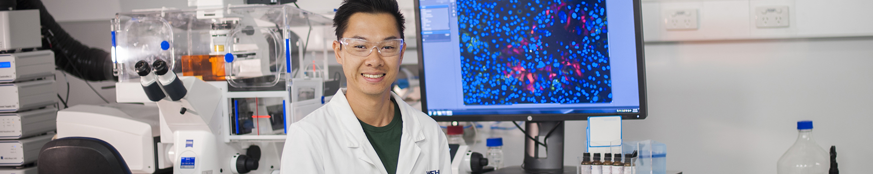 Dr Tan Nguyen in front of a microscope