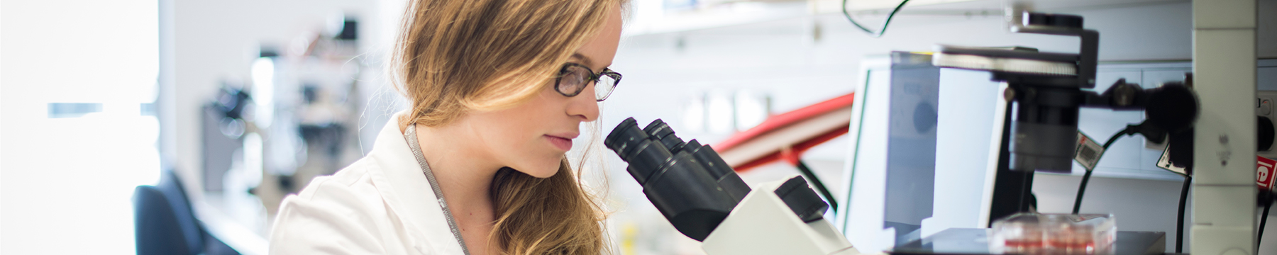 Female researcher at a microscope