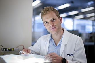 Dr Justin Boddey in a laboratory with a light box