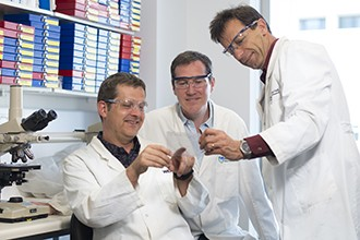 Dr Michael Buchert, Dr Toby Phesse, Associate Professor Matthias Ernst looking at gel photo