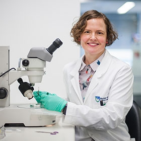 Dr Joanna Groom at a microscope