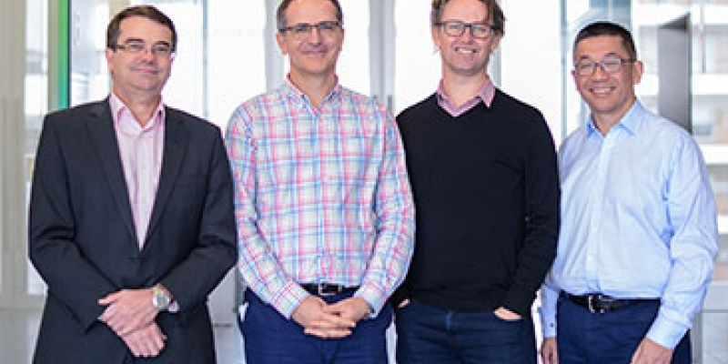 Four male scientists smiling at camera
