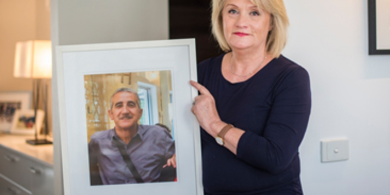 Kathy holding a photo of her late husband George