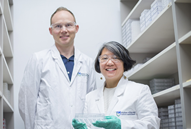 Researchers standing in laboratory, smiling at camera