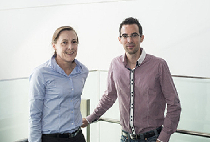 Two researchers standing in hallway smiling at camera