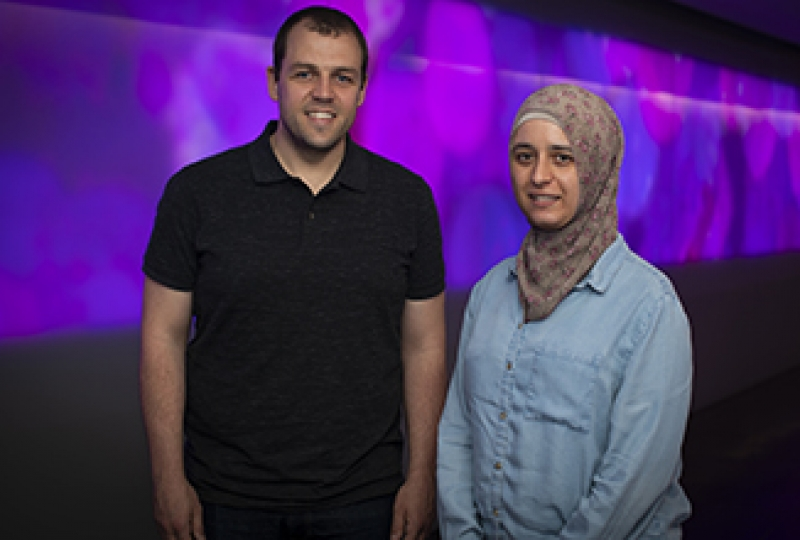 Two scientists smiling at camera, standing in front of purple screen