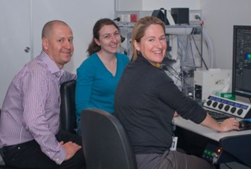 Doug Hilton, Kathy Potts and Kelly Rogers in front of a microscope