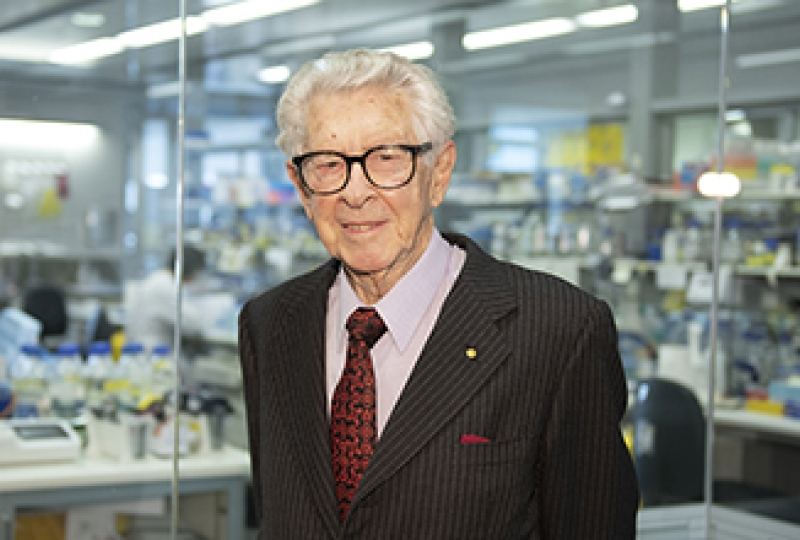 Professor Jacques Miller standing smiling at camera, with lab in the background