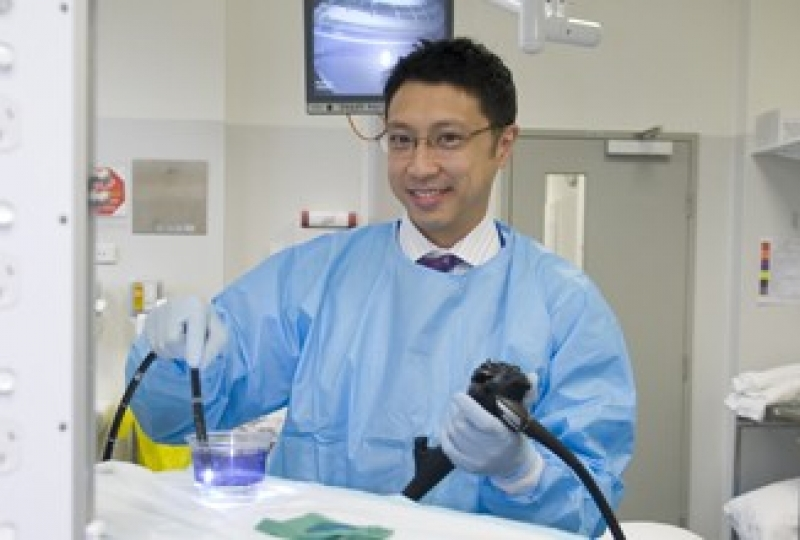 Dr Jason Tye-Din holding diagnostic equipment in a laboratory