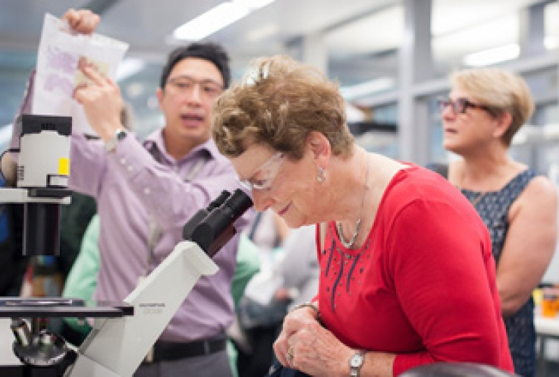 Dr Jason Tye-Din talks to the Coeliac Victoria and Tasmania group while a woman looks down a microscope