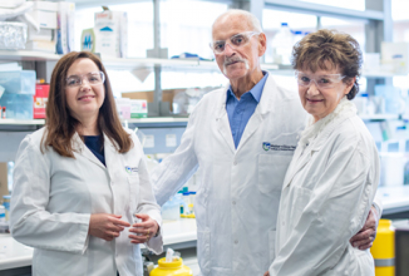 Researcher standing on the left in lab coat in a lab, with two other people also in lab coats