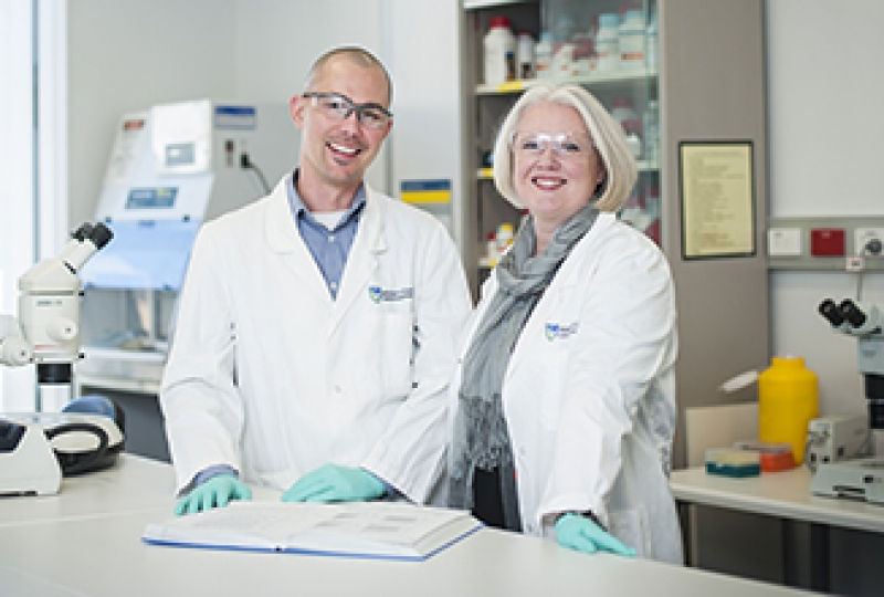 Two researchers standing in laboratory smiling at camera