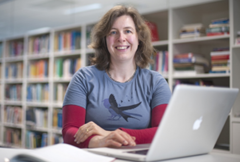 Associate Professor Melanie Bahlo sitting at desk with computer, library books in background