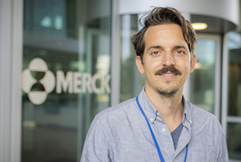 """Researcher smiling with sign saying """"Merck"""""""
