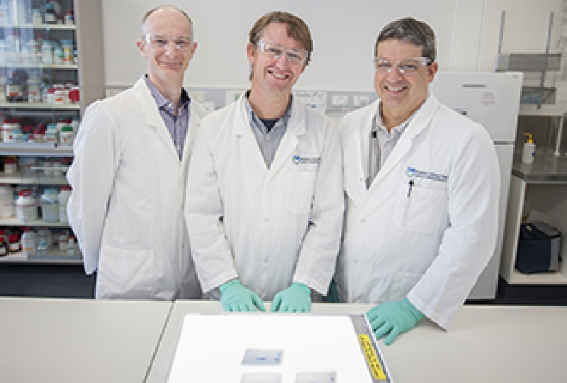 Three researchers standing in a laboratory smiling, with a light box in front of them