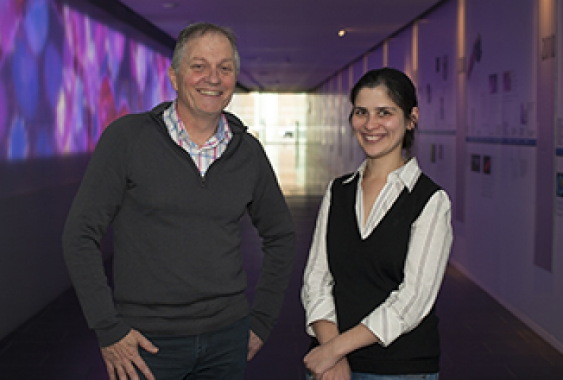 Two scientists standing smiling at camera in a long hallway with animation in the background.