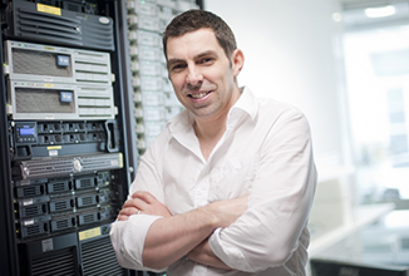 Researcher standing with arms crossed in front of computer server, smiling at camera