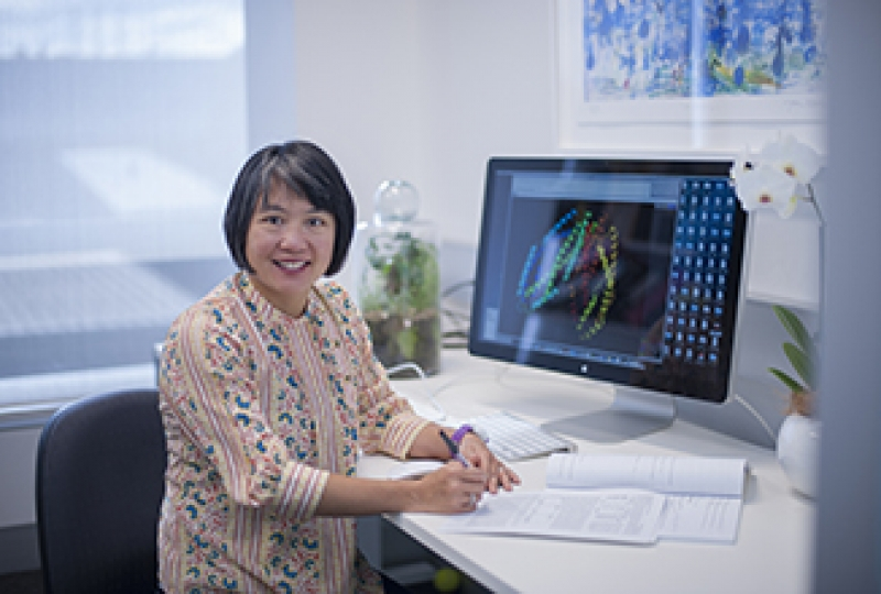 Researcher sitting in front of computer, writing and smiling at camera