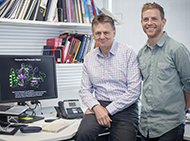 Alan Cowman sits on a desk, Justin Boddey stands beside him. Behind Cowman is a computer screen showing the 3D image.