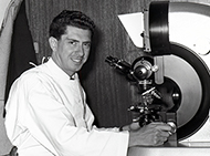 Historic photo of man at microscope, smiling at camera