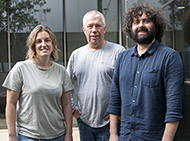 Three researchers standing outside a building