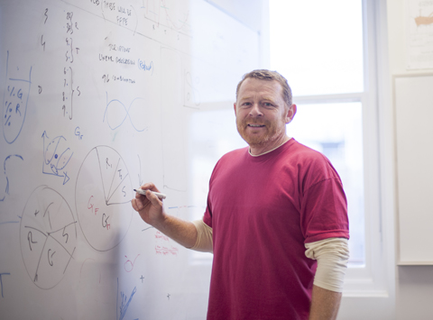 Professor Liam O'Connor writing mathematical equations on a white board