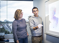 Two researchers working at a whiteboard
