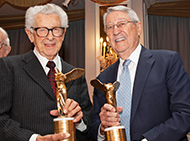 Two men holding award trophies