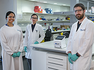 Three researchers in a laboratory with model diagnostic device