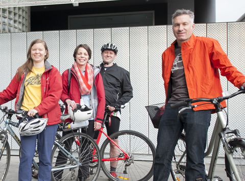 Staff stand with their bicycles on the institute Parkville forecourt