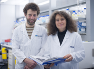 Dr Tim Thomas and Dr Anne Voss standing in lab with notebook