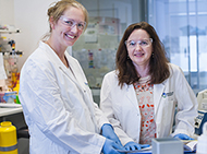 Two female scientists standing in the lab, smiling at the camera