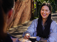 Woman sitting at an outdoor cafe and smiling