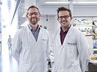 Two male researchers standing in a laboratory