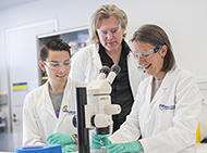 Three researchers looking at a microscope in the lab
