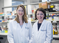 Two researchers smiling at the camera