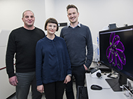 Three researchers with monitor showing parasite